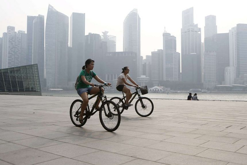 People ride bicycles past the central business district.
