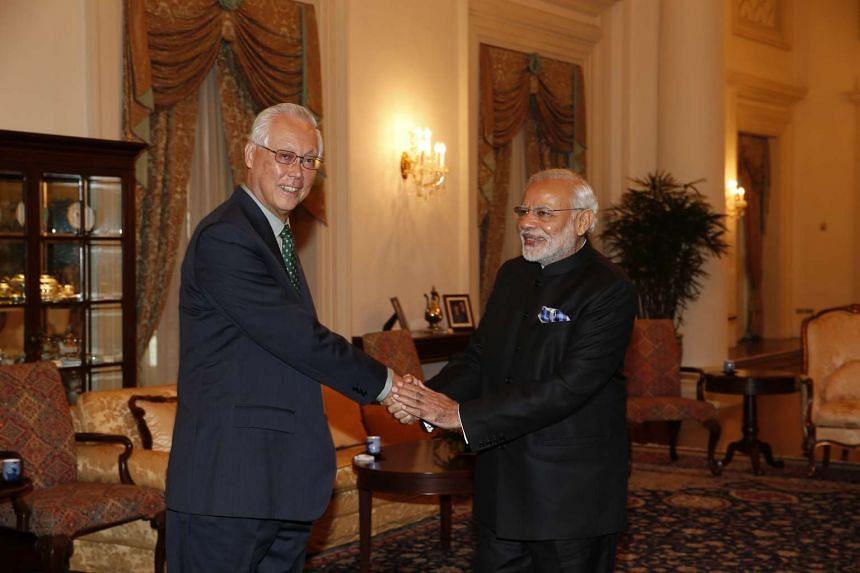 ESM Goh Chok Tong (left) shaking hands with Mr Modi.
