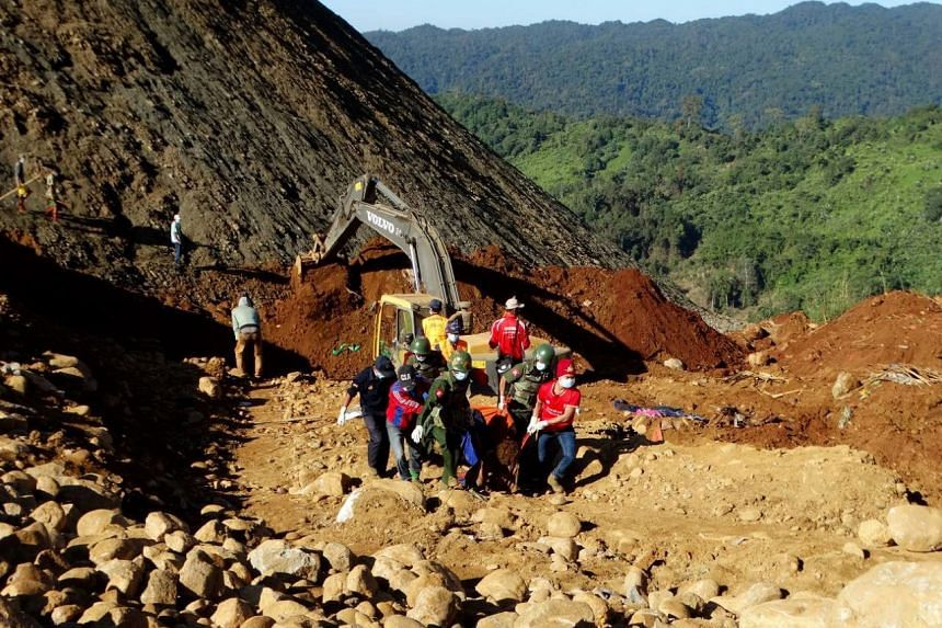 Rescue workers carry the body of a miner that was killed in the landslide at Hpa Kant jade mining area.