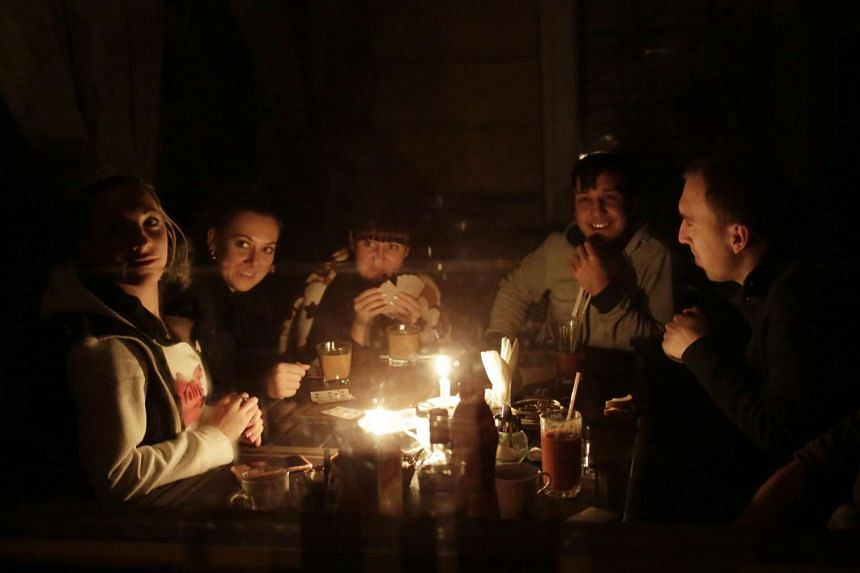 People play cards by candlelight in Crimea during the blackout on Nov 22, 2015.