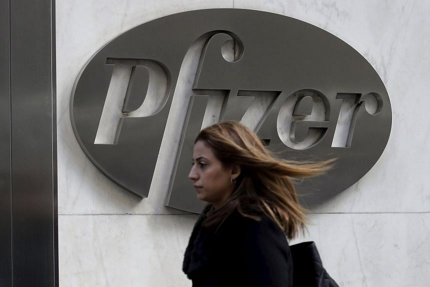A woman passes by the Pfizer World Headquarters building in the Manhattan borough of New York, on Nov 23, 2015.