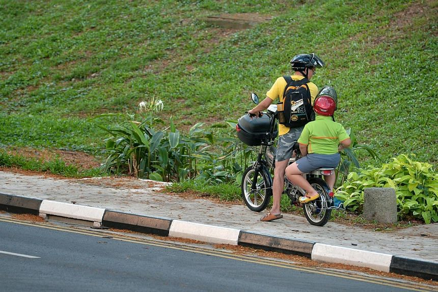 A man checking with his son who was riding pillion on his motorised bicycle on a pavement along Jurong West St 52.