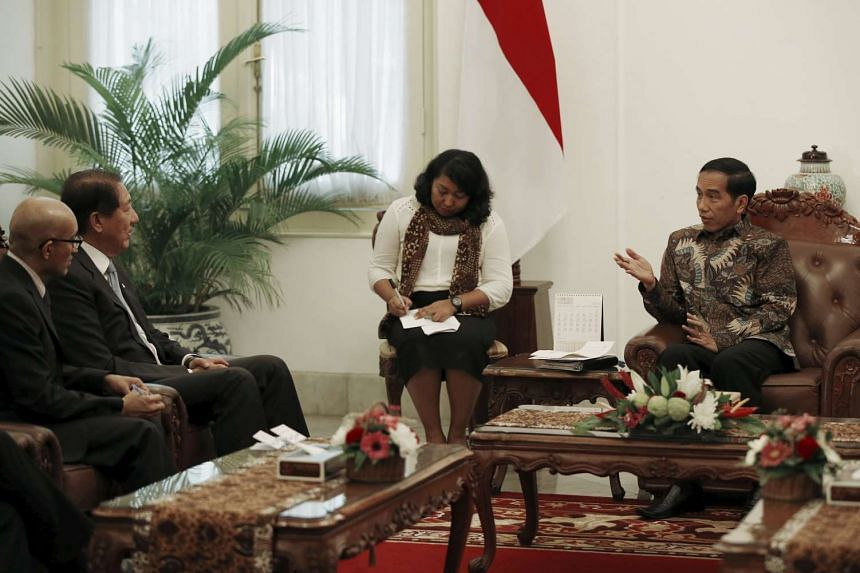 Indonesia's President Joko Widodo (Right) chats with Singapore's Deputy Prime Minister and Coordinating Minister for National Security Teo Chee Hean.