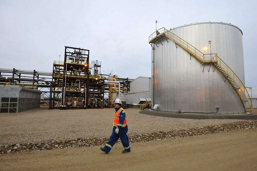 An oilfield worker walking past the Statoil oil sands facility near Conklin, Alberta, in this Nov 3, 2011, file photo.