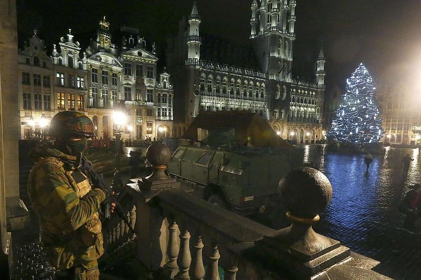A Belgian soldier standing guard over the Grand-Place of Brussels as police searched the area on Sunday following the recent deadly Paris attacks. Armed police and troops have been patrolling the near- deserted streets of Brussels all weekend after t