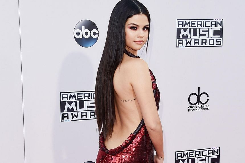 On the red carpet, singers Selena Gomez (above) wore a sequinned backless dress while Demi Lovato dazzled in a 1920s flapper-style gown.