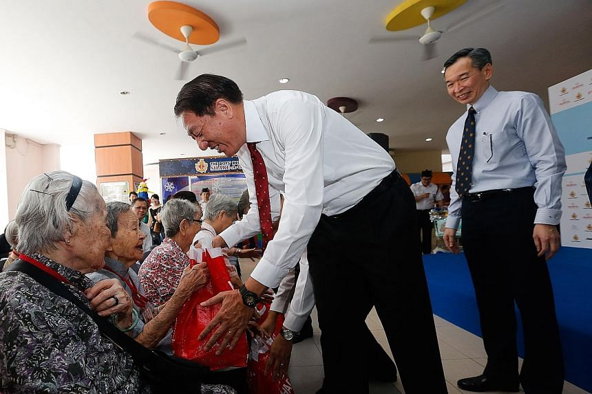 Deputy Prime Minister Teo Chee Hean presenting food hampers to beneficiaries from Kheng Chiu Happy Lodge yesterday. He is accompanied by Mr Lui Chong Chee, the organising committee chairman of the Boys' Brigade's Share-a-Gift project. Mr Lui said tha