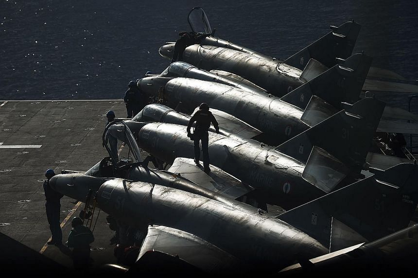French navy personnel working on warplanes. Russia said its strikes had destroyed facilities near ISIS' stronghold of Raqqa, which is also the target of French air strikes.