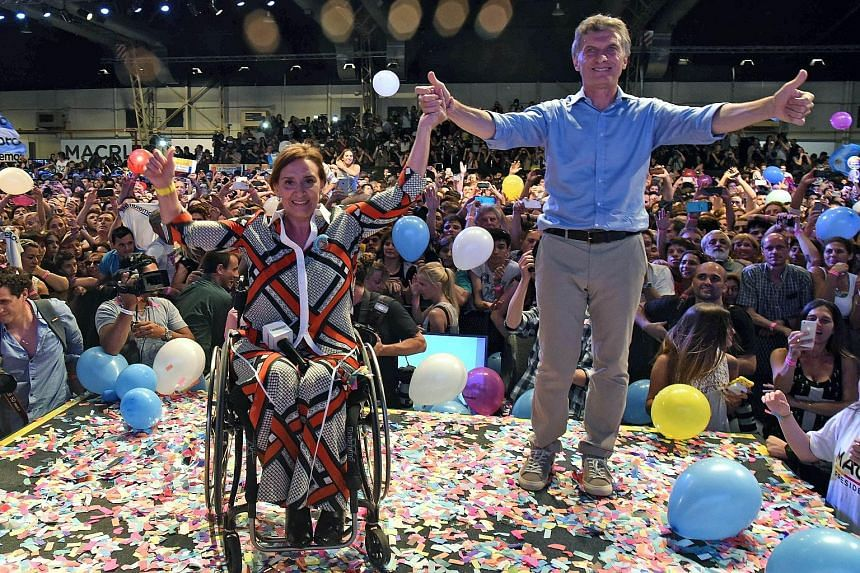 Mr Mauricio Macri and his running mate, Ms Gabriela Michetti (who has to use a wheelchair after being seriously injured in a car accident in 1994), celebrating in Buenos Aires on Sunday, after getting early results of the presidential run-off electio
