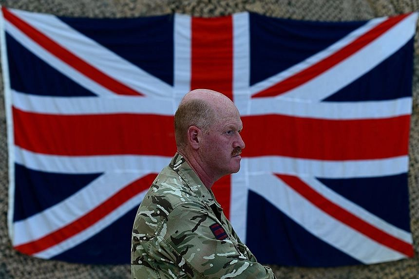 A British military officer in front of the Union Jack. Prime Minister David Cameron was to present the full £178 billion (S$383 billion) spending plan for the British military over the next decade in Parliament yesterday.