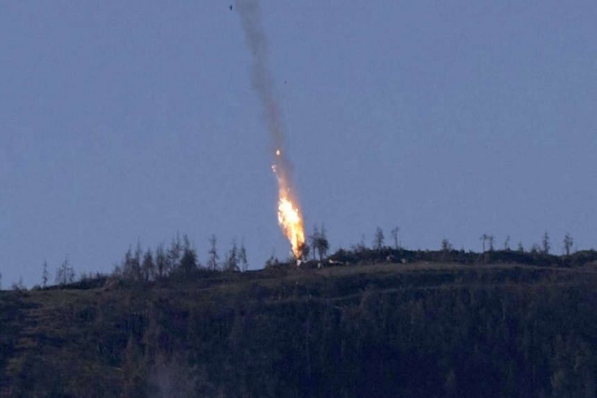 A still image made available on Nov 24, 2015 from a video footage shown by the HaberTurk TV Channel shows smoke billowing from what was described as the crash site of a plane after it was shot down near the Turkish-Syrian border.