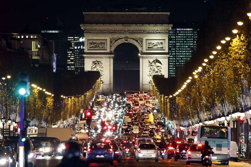 Christmas holiday lights hang from trees to illuminate Champs Elysees avenue in Paris.