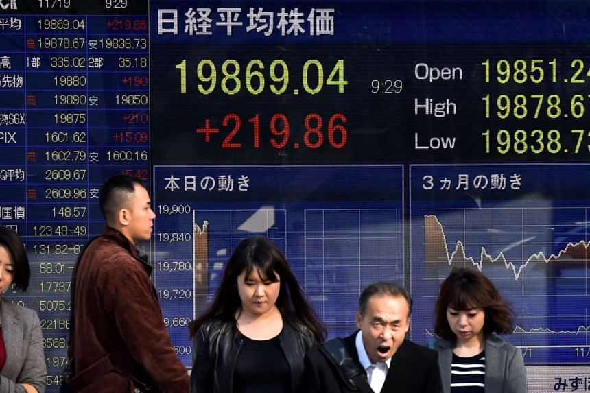 Pedestrians walking past a share prices board of the Tokyo Stock Exchange in Tokyo on Nov 19, 2015.