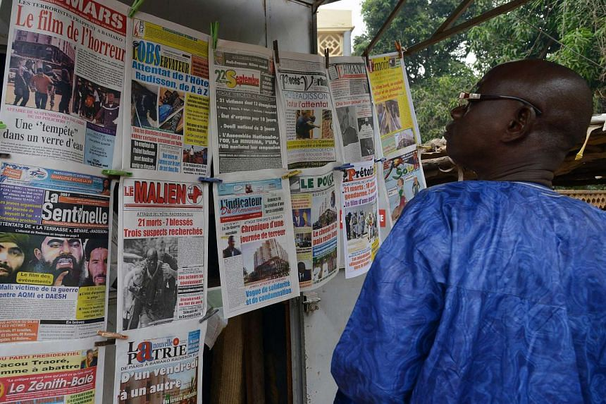 A man looking at the frontpages of newspapers at a newsstand in Bamako on Nov 23, 2015, three days after a deadly attack at the Radisson Blu hotel.