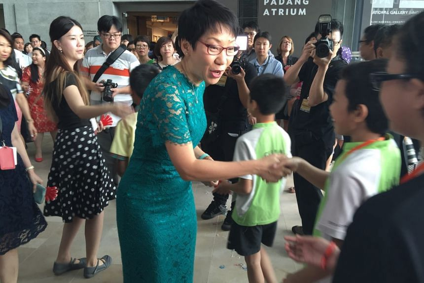 """Minister for Culture, Community and Youth Grace Fu gives out """"First Guest"""" stickers to schoolchildren during the opening of The National Gallery Singapore."""