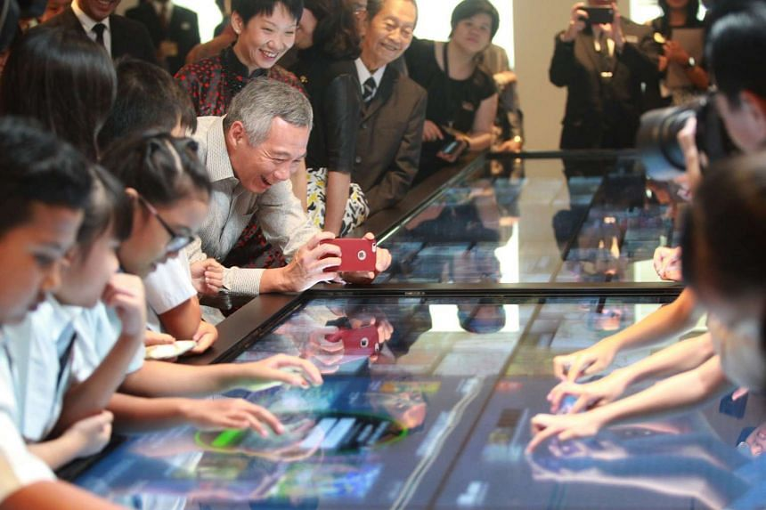 PM Lee (centre) taking a picture of pupils from Greenwood Primary at the Social Table during his visit to National Gallery Singapore on Nov 23, 2015.