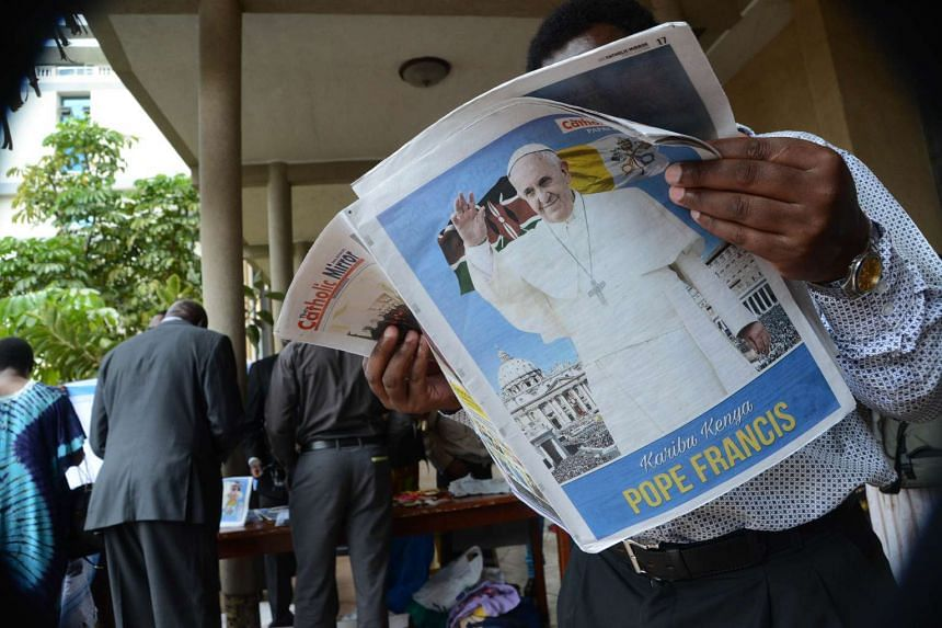 A man reads a copy of the Catholic Mirror newspaper bearing an image of Pope Francis at the Holy Family Basilica in Nairobi on Nov 22, 2015.