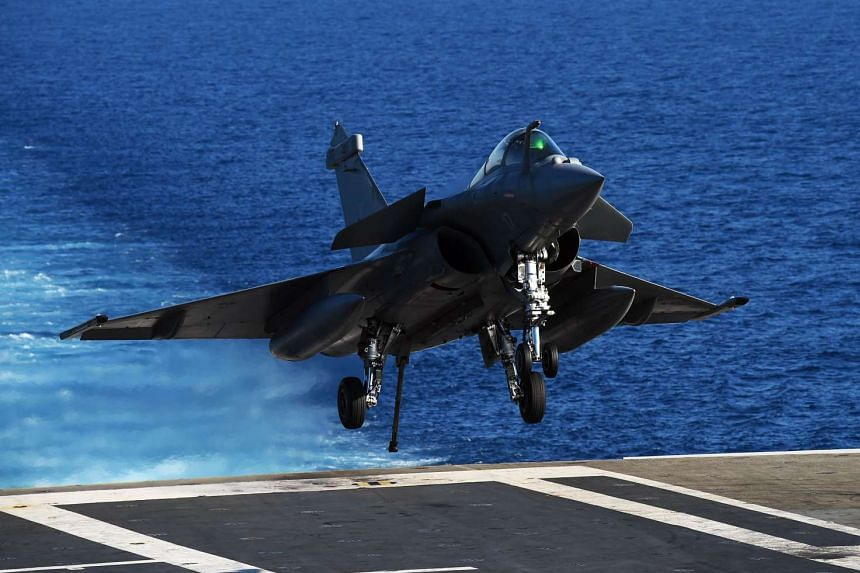 A French Rafale jet fighter lands on the aircraft carrier Charles-de-Gaulle on Sunday.