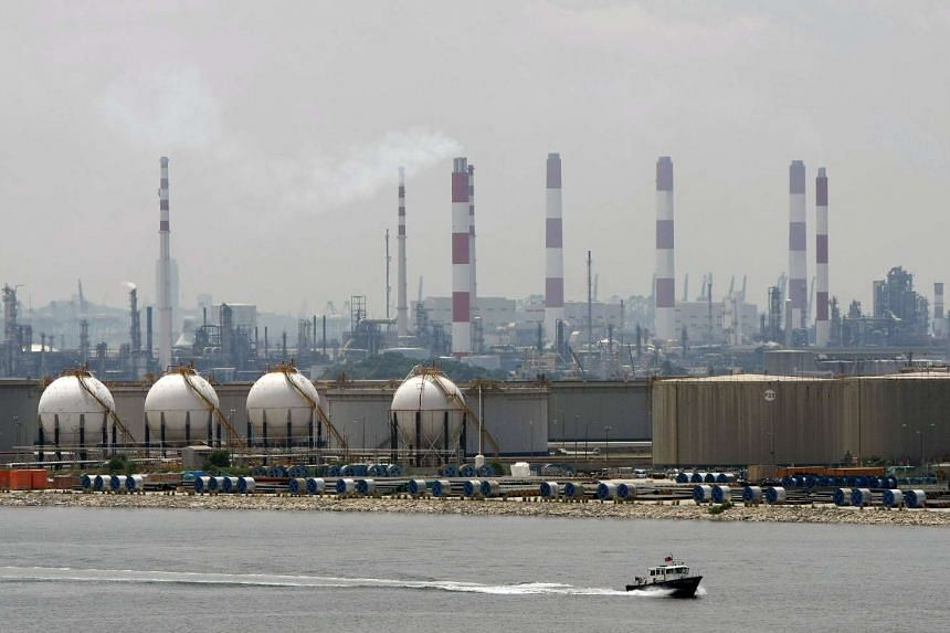 A boat passes in front of an oil refinery located on Singapore's Jurong Island.