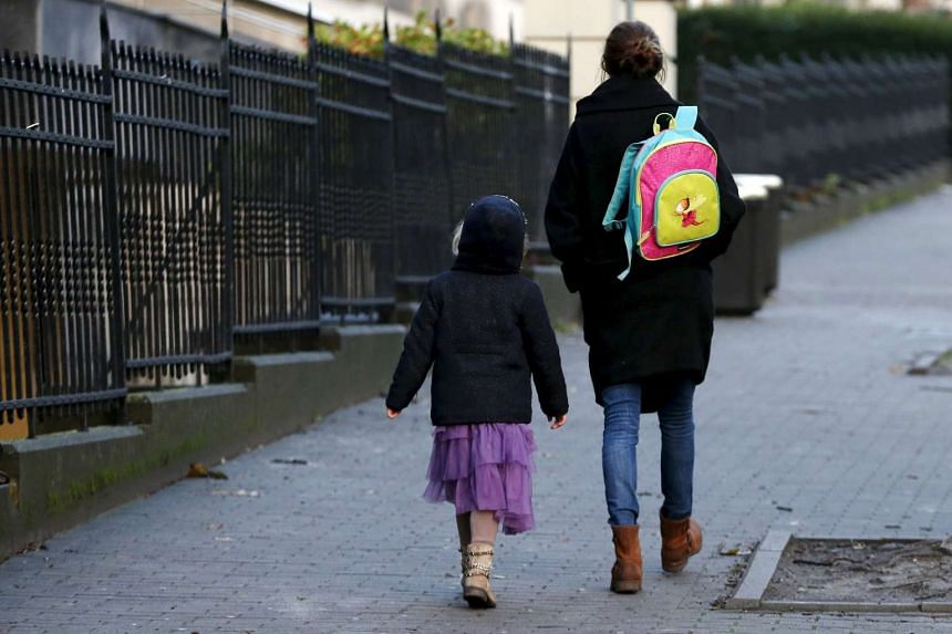 A woman accompanies her daughter to school in Brussels on Nov 25, 2015.