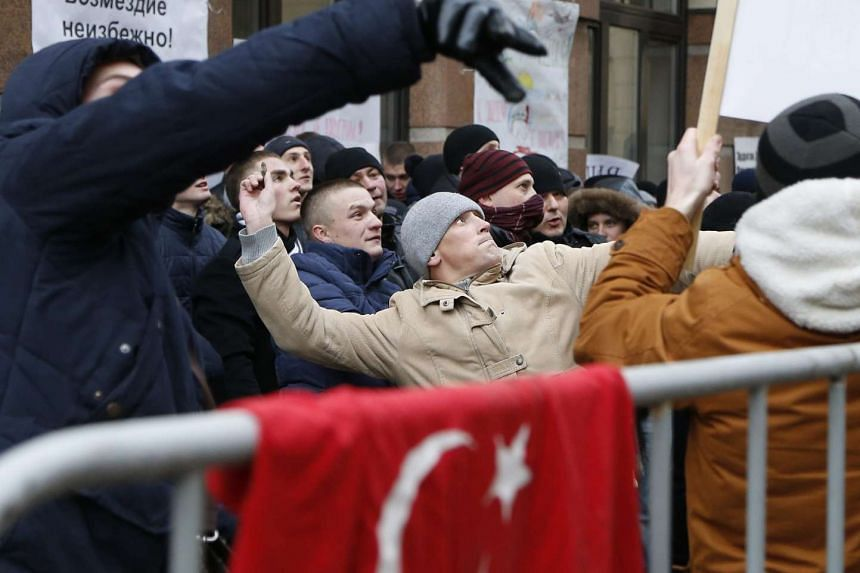 Russian people throw stones as they protest in front of the Turkish embassy in Moscow, Russia on Nov 25, 2015.