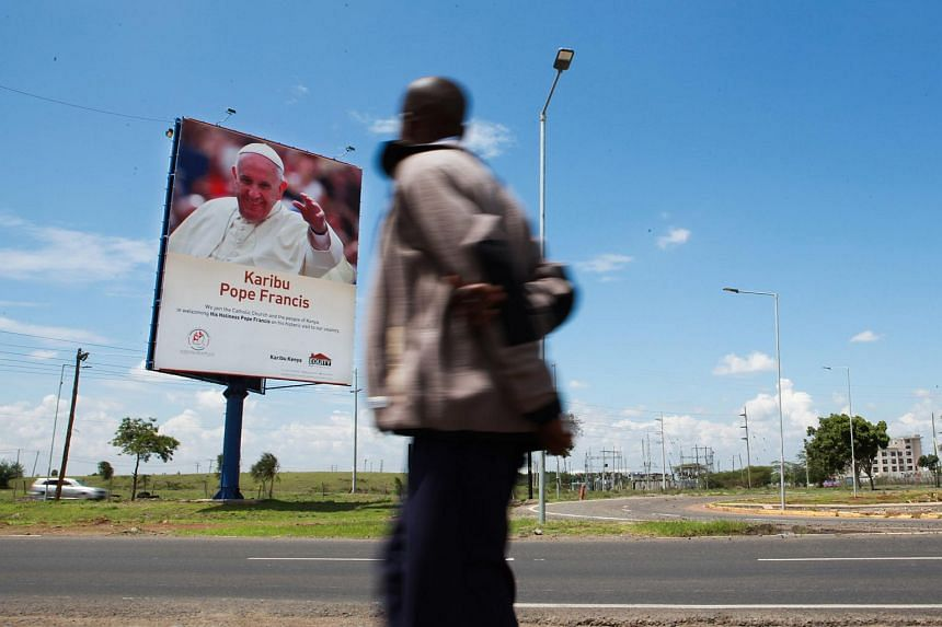A pedestrian walks past a billboard welcoming Pope Francis to the country at the Jomo Kenyatta International Airport, in Nairobi, Kenya on Nov 23, 2015.