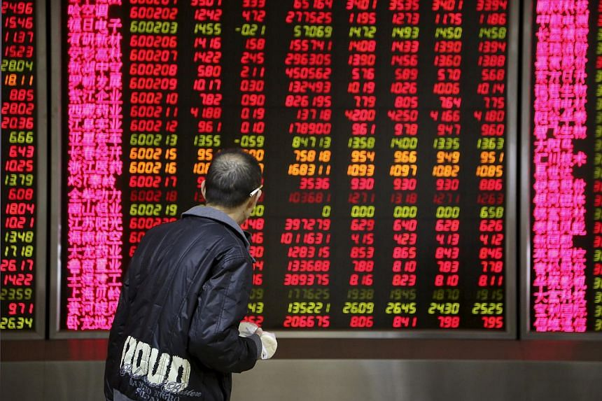 A man walking past an electronic board showing stock information at a brokerage house in Beijing, China.