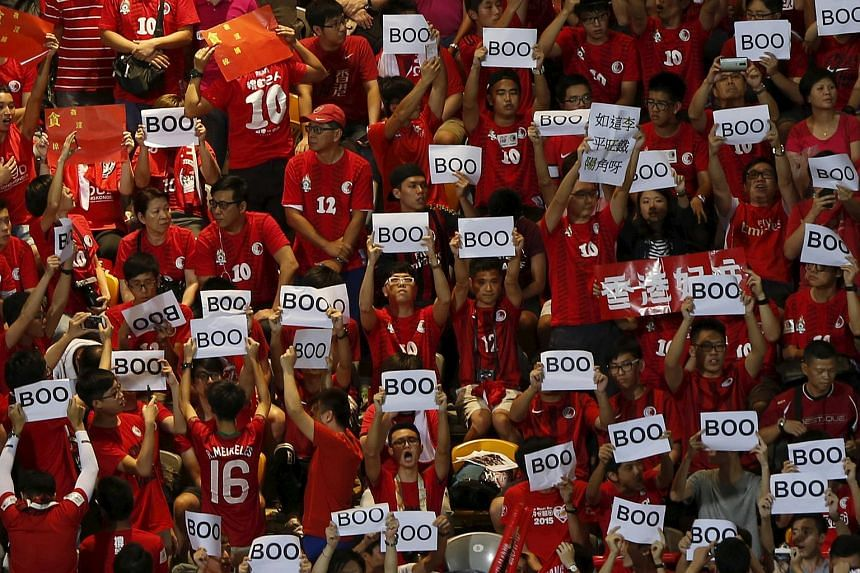 "Hong Kong fans hold ""boo"" signs, during the Chinese national anthem at the 2018 World Cup qualifying match between Hong Kong and China."