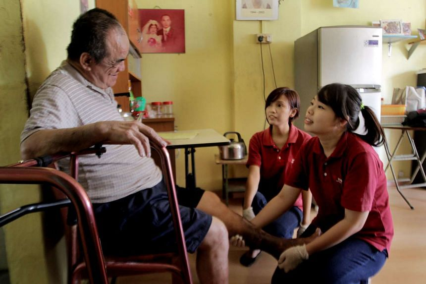 Touch Community Services workers helping Mr Tan Ba Bee, who is blind, wash his feet at his home.