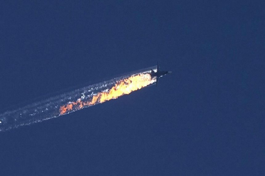 A still image made available on Nov 24, 2015, from video footage shown by the HaberTurk TV Channel shows a burning trail as a plane comes down after being shot down near the Turkish-Syrian border, over north Syria.