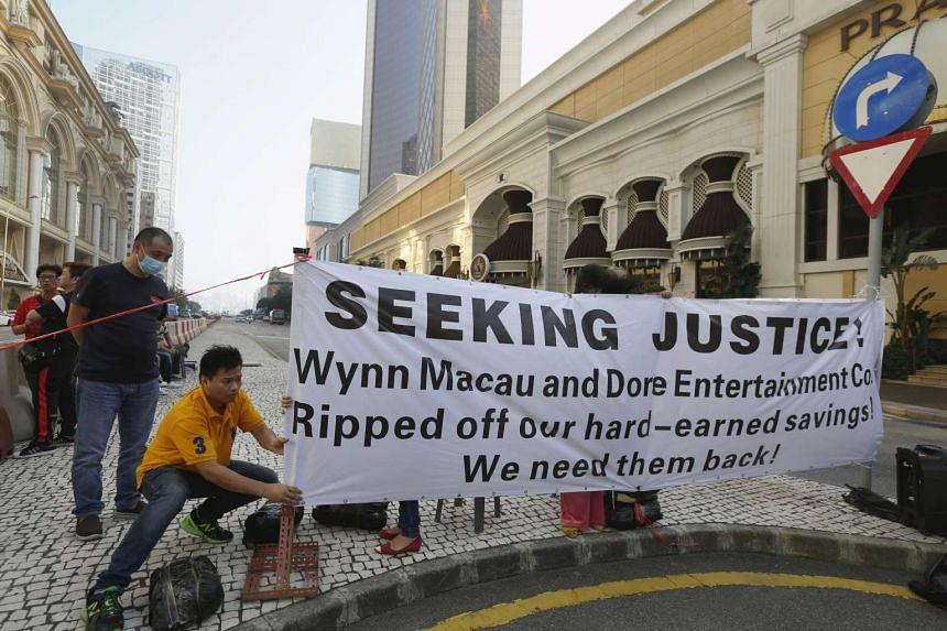 A protester adjusts a banner outside Wynn Macau, Nov 20, 2015.