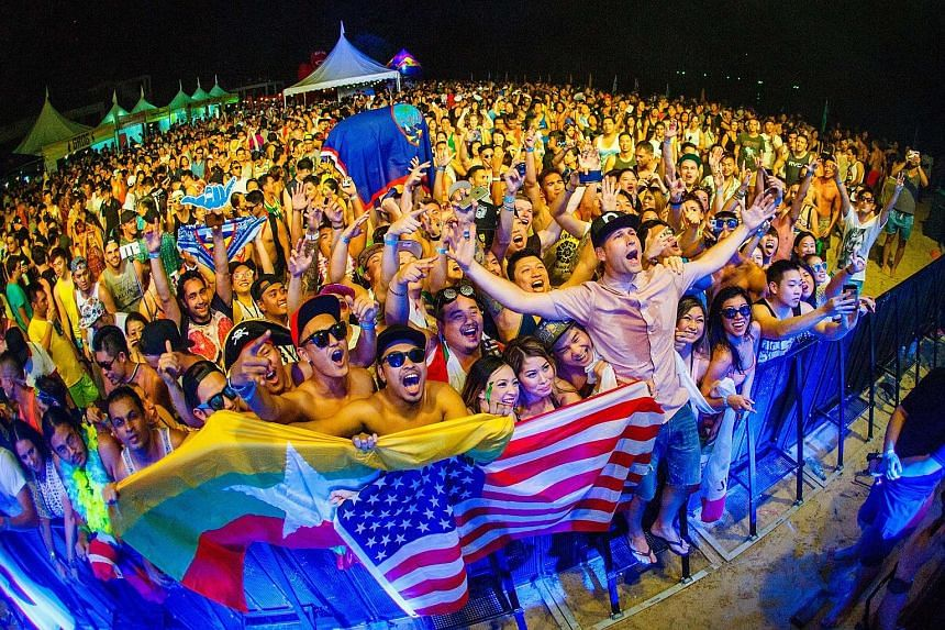 Dutch DJs Showtek took the stage on the ship on the first day; and partygoers with DJ Kaskade (above, in shirt and cap) in Langkawi.