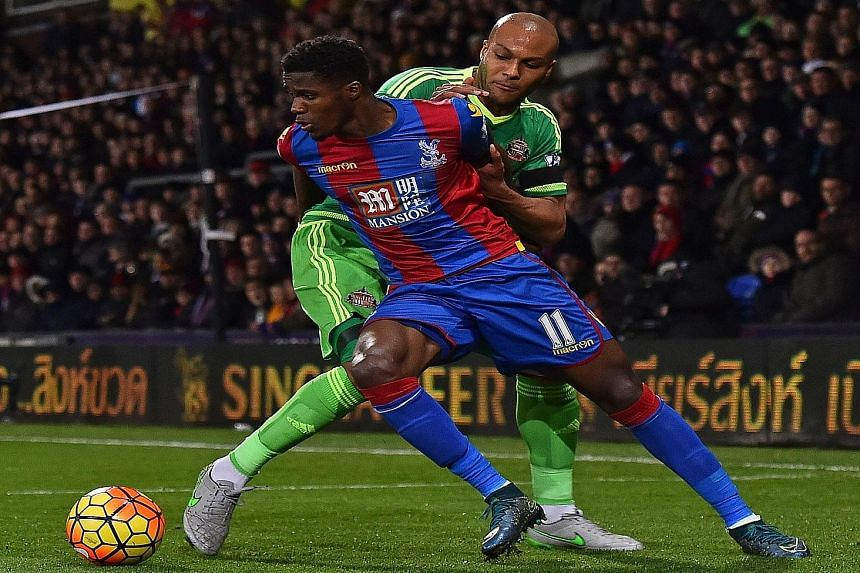 Sunderland defender Younes Kaboul (in green) trying to dispossess Crystal Palace striker Wilfried Zaha. Despite winning 1-0, the Black Cats remain in the relegation zone.