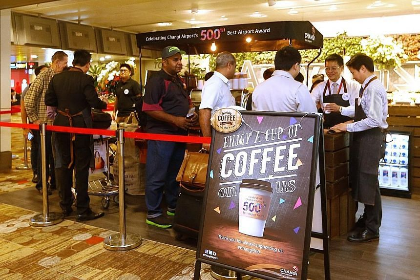 """Top executives from Changi and its airport partners donned aprons and rolled up their sleeves to serve hot coffee to travellers and staff yesterday morning. The coffee giveaway was a small gesture to say """"thank you"""" for the support over the years, wh"""