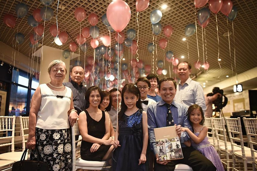 Kylie Tan (centre), seven, her siblings Brian (back, with bow tie), 11, and Sarah (far right), six, with their parents Tan Chin Hwee (right) and Michelle Lee (left, in black) and their extended family at yesterday's book launch.