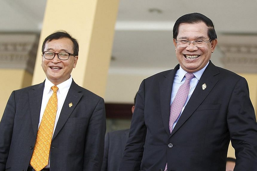 Mr Sam Rainsy (far left), Cambodia's most prominent opposition leader, and Prime Minister Hun Sen in less fraught times. An arrest warrant has been issued for Mr Sam Rainsy after his verbal spat with the strongman Premier.