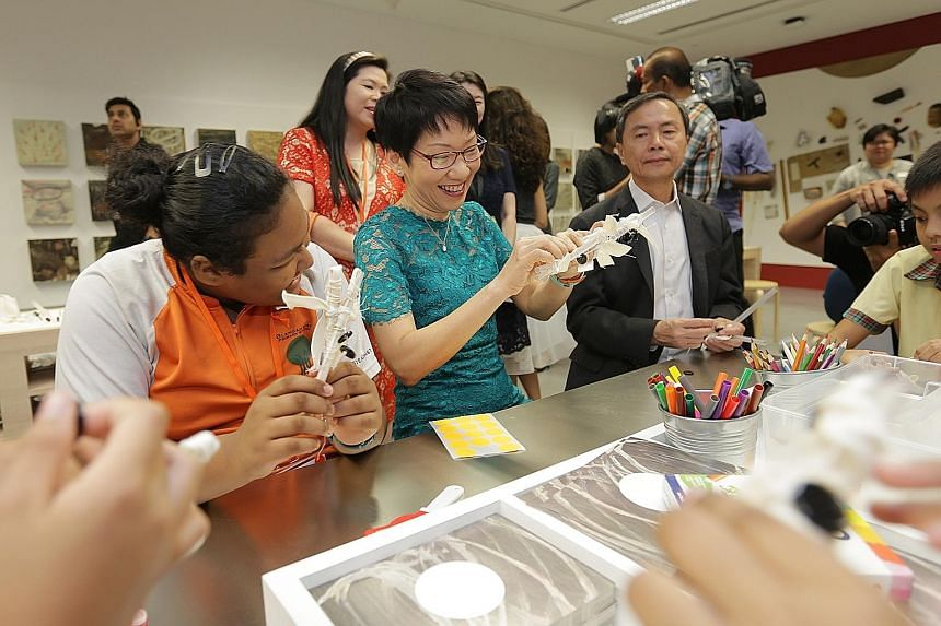 Minister for Culture, Community and Youth Grace Fu (above) interacting with visitors at the National Gallery Singapore's Keppel Centre For Art Education yesterday. With her was museum chairman Hsieh Fu Hua. Many visitors (below) were in high spirits