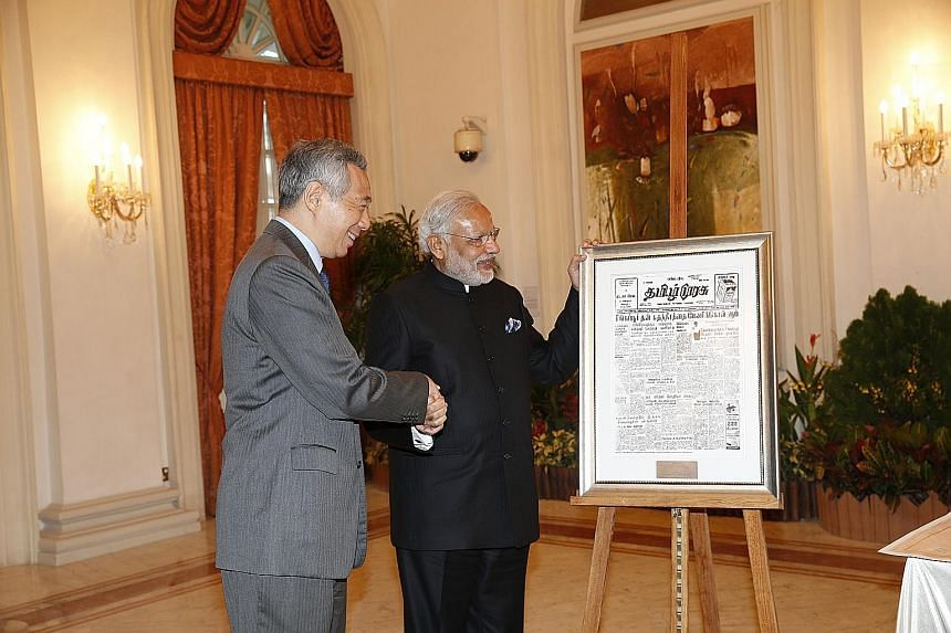 Mr Modi calling on President Tony Tan Keng Yam at the Istana yesterday. (Right) Mr Lee presenting a special gift of the front page of Tamil Murasu dated Aug 11, 1965, to Mr Modi. It carries the news of India officially recognising the then newly inde