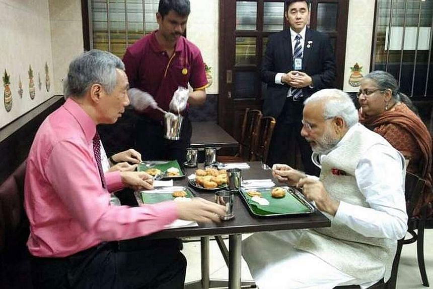 PM Lee and Mrs Lee (hidden) having a meal with Mr Modi at Indian vegetarian restaurant Komala Vilas on Monday night.