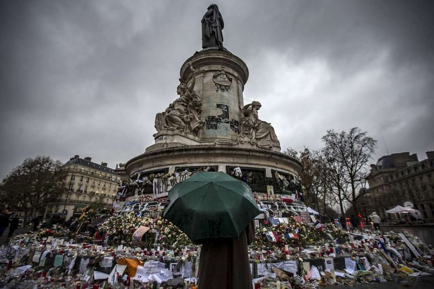 A pedestrian with an umbrella pauses in front of the memorial of candles and flowers for the victims of the Nov 13 Paris attacks, on Place de la Republique in Paris, France, on Nov 24, 2015.