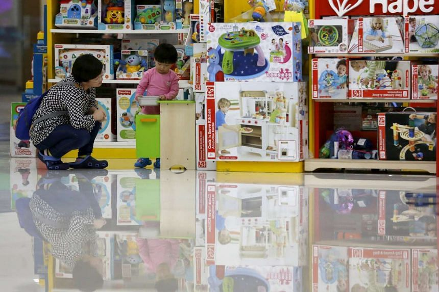 A parent plays with her daughter at a toy shop in Beijing, China, Oct 30, 2015.