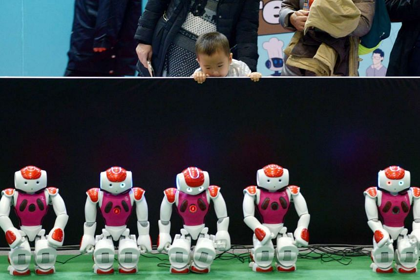 A boy looking at a display of robots at the World Robot Conference in Beijing on Nov 24.