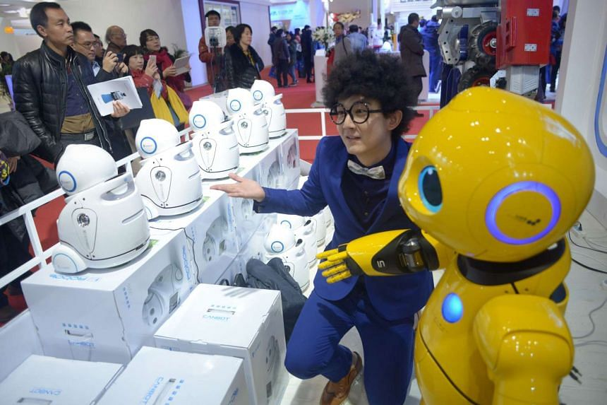 A visitor posing for a photo with a robot at the World Robot Conference in Beijing on Nov 24.