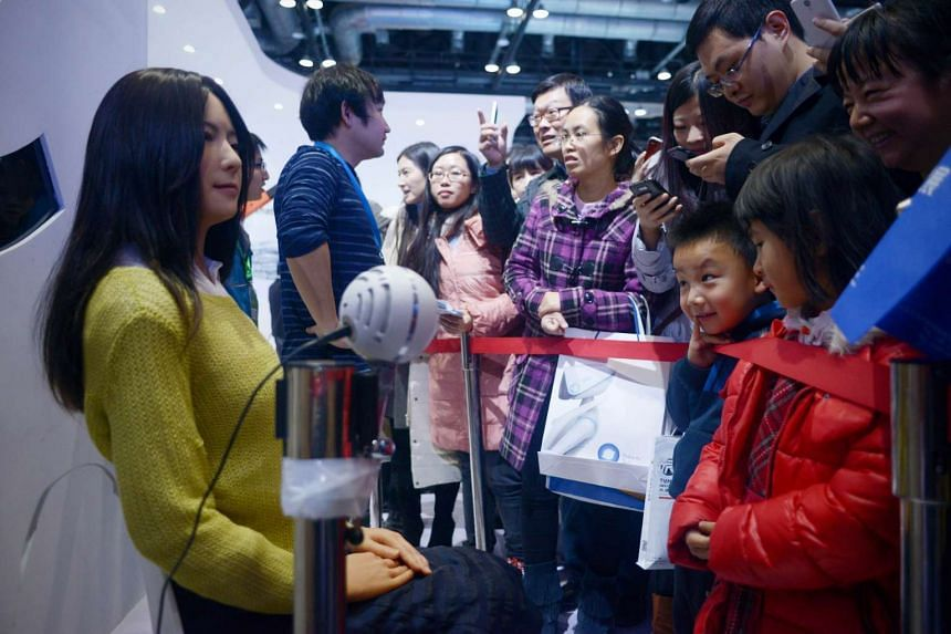 Visitors watching a robot demonstration (left) at the World Robot Conference in Beijing on Nov 24.
