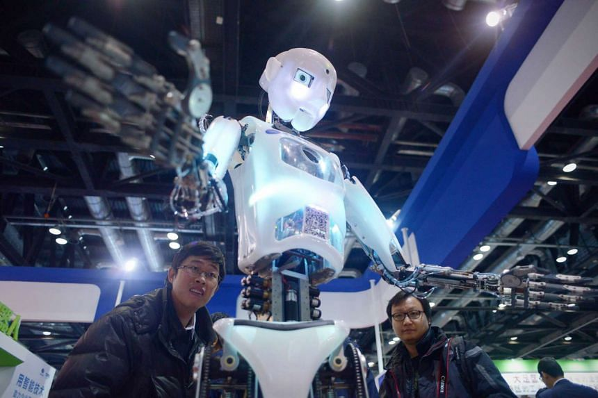 Visitors watching a robot demonstration (centre) at the World Robot Conference in Beijing on Nov 24.