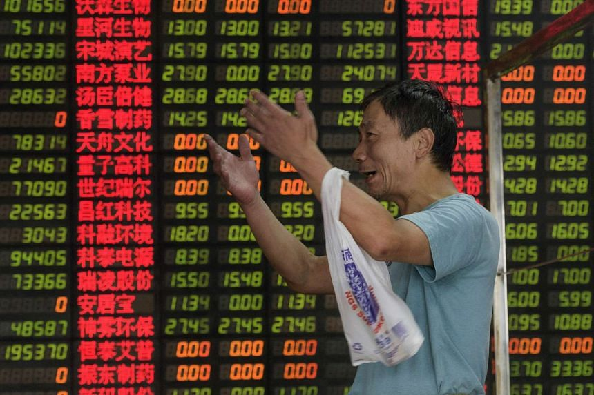 An investor reacting in front of screens showing stock market movements at a brokerage house in Shanghai on Sept 1.