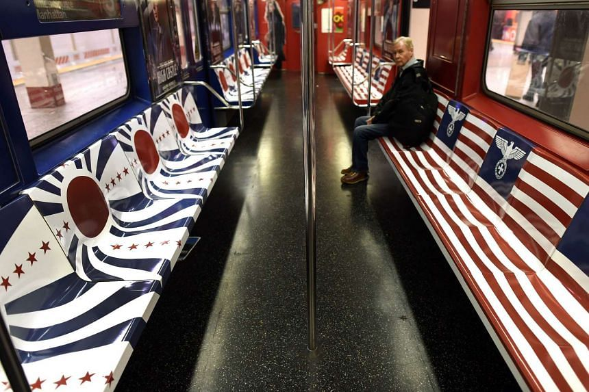 A passenger sits on a New York City Subway train covered in symbols from Nazi Germany and Imperial Japan.