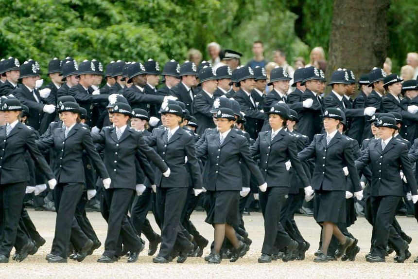 Metropolitan Police officers march in formation at Horse Guards Parade in London.
