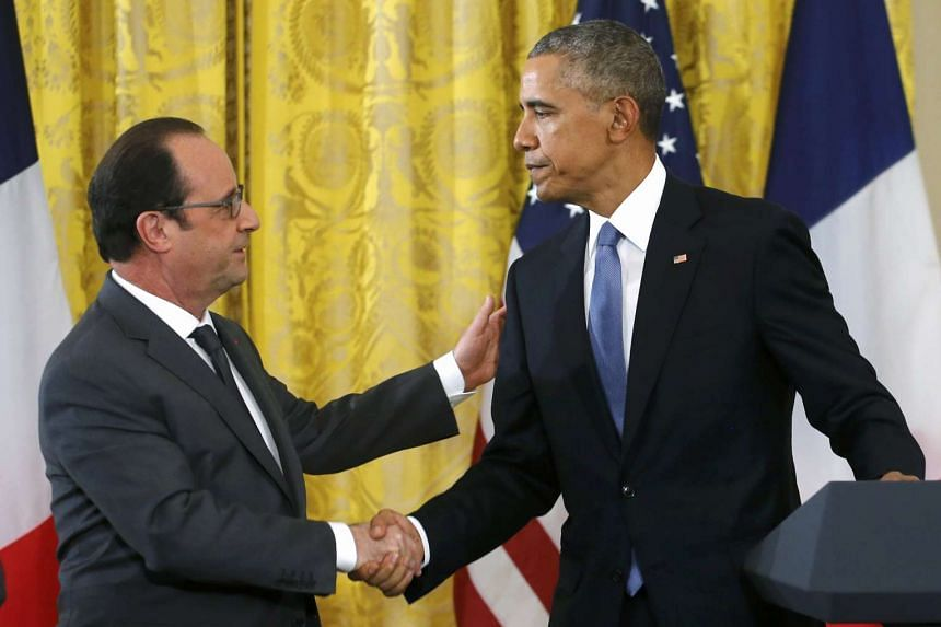 US President Barack Obama (right)  greets French President Francois Hollande during a joint news conference on Tuesday.