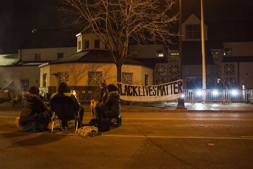 A group gathers outside of a police station after five  people were shot at a protest in Minneapolis,. Minnesota on Tuesday.